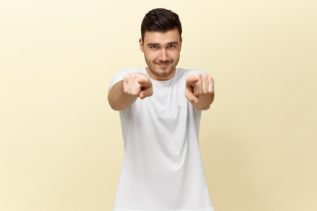 Knappe zelfverzekerde positieve jonge kerel in wit casual t-shirt naar voren wijzend