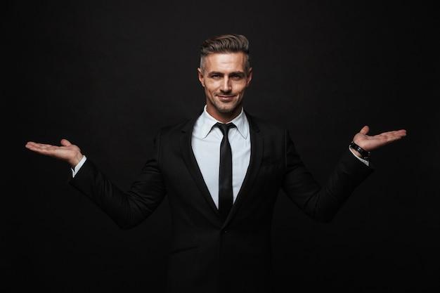 Knappe zelfverzekerde zakenman die een pak draagt dat geïsoleerd over een zwarte muur staat en kopieerruimte presenteert