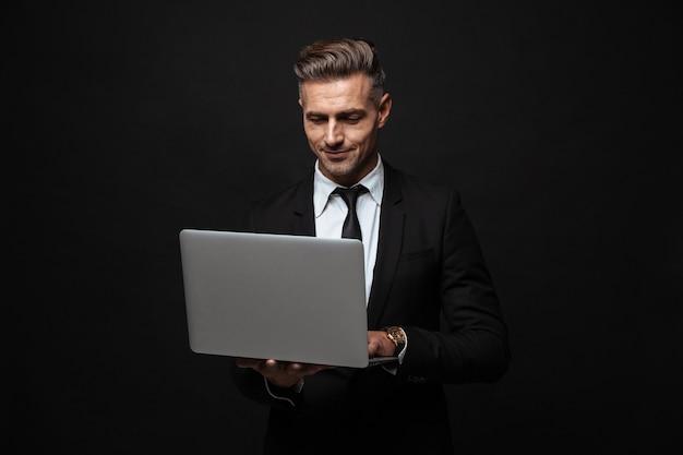 Knappe zelfverzekerde zakenman die een pak draagt dat geïsoleerd over een zwarte muur staat en op een laptop werkt