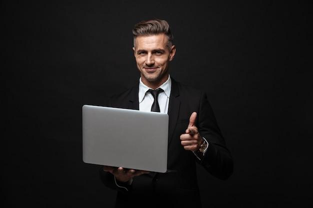 Knappe zelfverzekerde zakenman die een pak draagt dat geïsoleerd over een zwarte muur staat, op een laptop werkt, met de vinger naar de camera wijst