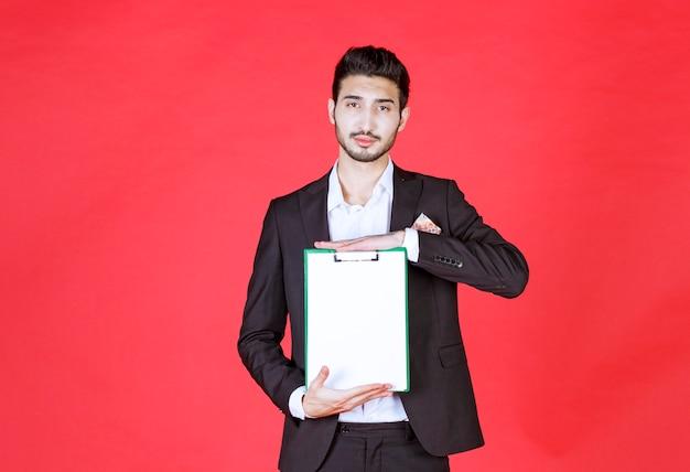 Knappe zelfverzekerde zakenman die een pak draagt en een notitieblok vasthoudt