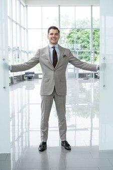 Knappe zelfverzekerde zakenman in pak die het kantoor binnenkomt.