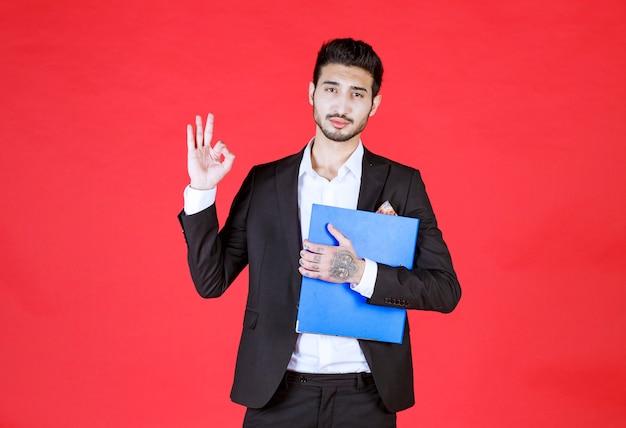 Knappe zelfverzekerde zakenman in pak met notitieblok doet ok teken