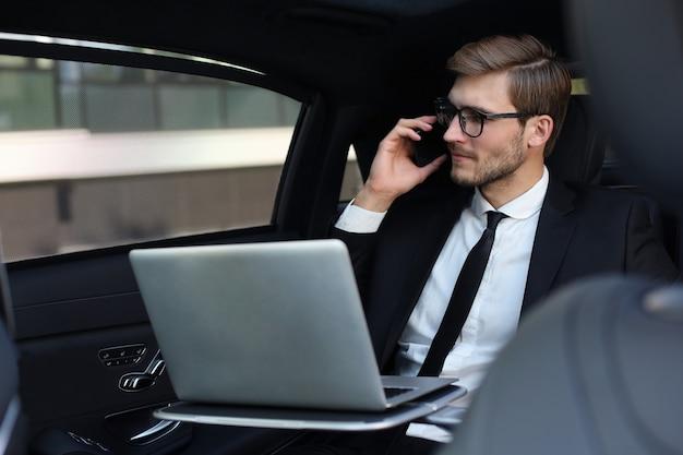 Knappe zelfverzekerde zakenman in pak praten op slimme telefoon en werken met behulp van laptop zittend in de auto.