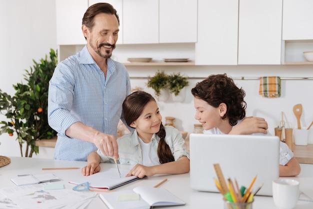 Knappe zoon met golvend haar die veel aandacht besteedt aan zijn vader die een cirkel schrijft met een kompas terwijl zijn zus hem met een glimlach bekijkt