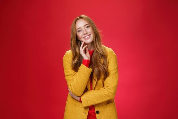 Knappe, zorgeloze en gelukkige ontspannen roodharige vriendin in gele stijlvolle jas die het gezicht aanraakt en het hoofd kantelt als lachend met positieve emoties, vrolijk poserend tegen een rode achtergrond.