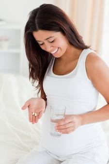 Knappe zwangere vrouw die een glas water en pillen houdt terwijl het zitten op een bed
