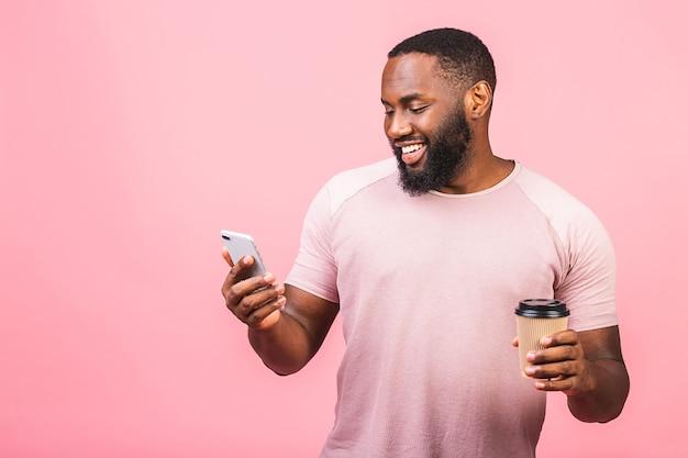 Knappe zwarte afrikaanse amerikaan met mobiele telefoon en koffiekop meenemen