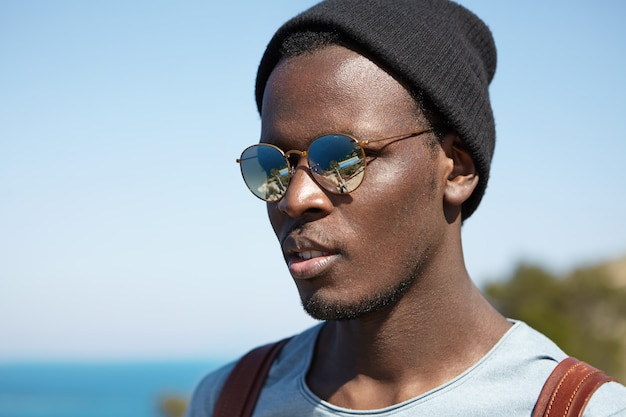 Knappe zwarte jonge hipster met stijlvolle hoed en ronde zonnebril met gespiegelde lens die mooie en gelukkige momenten van zijn reis in het buitenland bewondert terwijl hij alleen rond de wereld reist