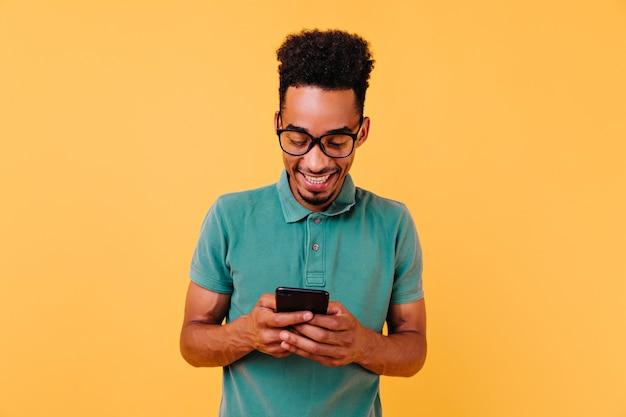 Knappe zwarte kerel die in grote glazen telefoonbericht leest. portret van tevreden afrikaanse man met smartphone.