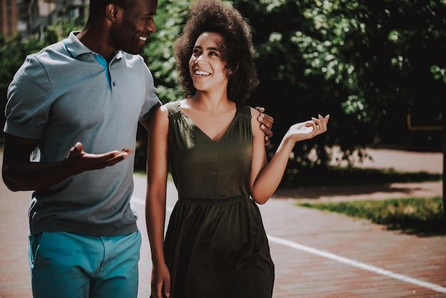 Knappe zwarte man en mooie vrouw lopend onderaan straat.