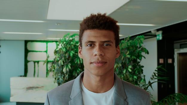 Knappe zwarte man in pak jonge afro-amerikaanse man in elegant pak die in een modern kantoor staat en vrolijk lacht naar de camera