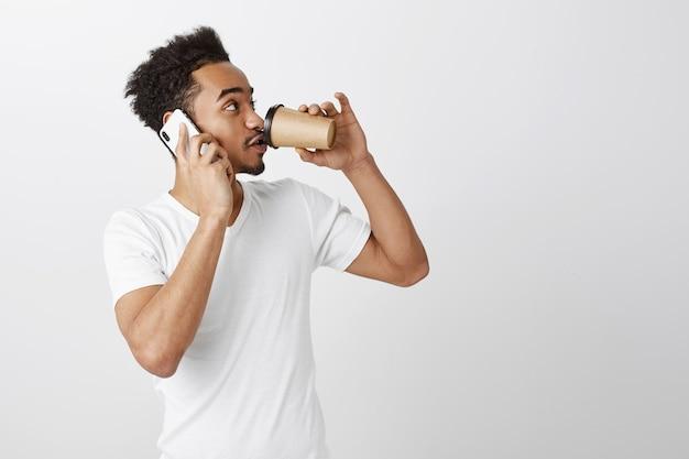 Knappe zwarte man in wit t-shirt praten op mobiele telefoon en afhaalmaaltijden koffie drinken, op zoek naar rechts