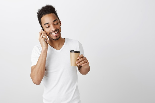 Knappe zwarte man in wit t-shirt praten op mobiele telefoon en afhaalmaaltijden koffie drinken