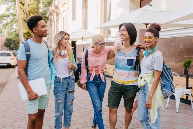 Knappe zwarte man met laptop kijken naar aziatische jongen in glazen, die schattige meisjes zachtjes omhelzen. studenten in stijlvolle kleding die samen op straat rondhangen en lachen.