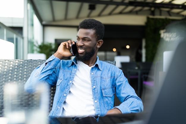 Knappe zwarte man praten over slimme telefoon, opzij kijken en glimlachen. hij is in een café-bar.