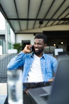 Knappe zwarte man praten over slimme telefoon, opzij kijken en glimlachen.