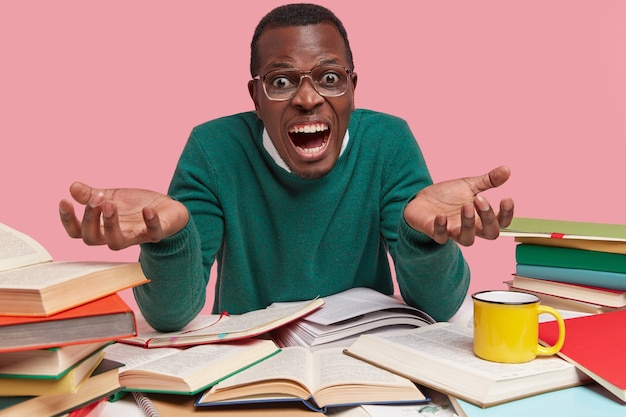 Knappe zwarte man spreidt handen met woede, draagt een groene trui, drukt negatieve gevoelens uit