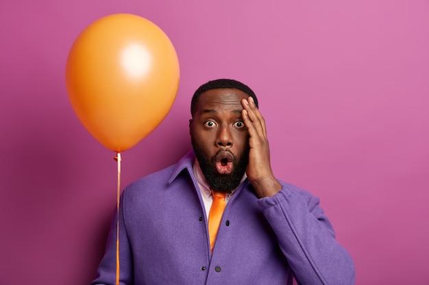 Knappe zwarte man staart met stomheid, raakt het hoofd aan, vergeet iemand op feestje uit te nodigen, geschokt door veel voorbereidingen, houdt ballon vast, draagt levendige outfit