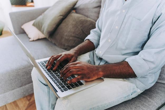 Knappe zwarte volwassen man aan het werk met computerlaptop thuis