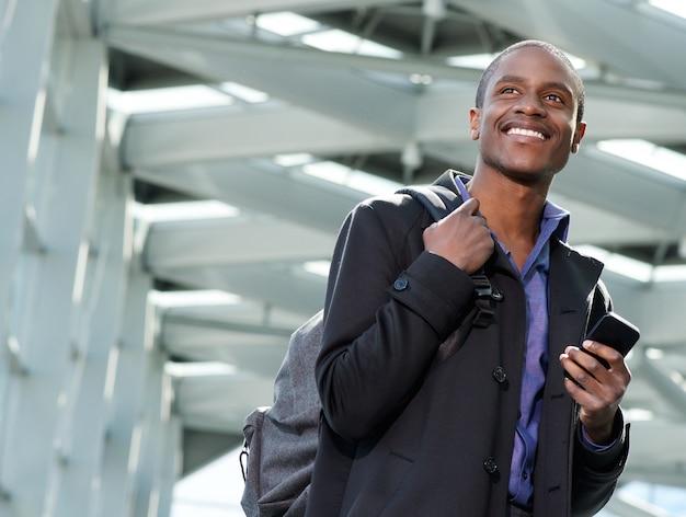 Knappe zwarte zakenman reist met tas en mobiele telefoon