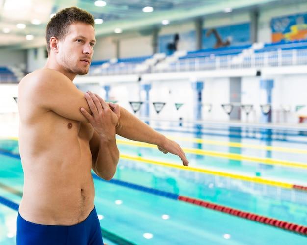 Knappe zwemmer die middelgroot schot uitrekt