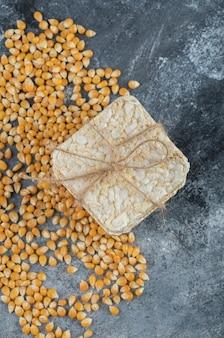 Knapperig brood in touw met ongekookte popcornzaadjes.