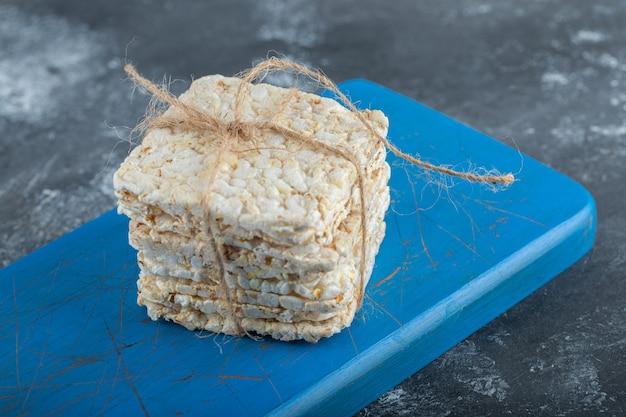 Knapperig brood in touw op een houten snijplank.