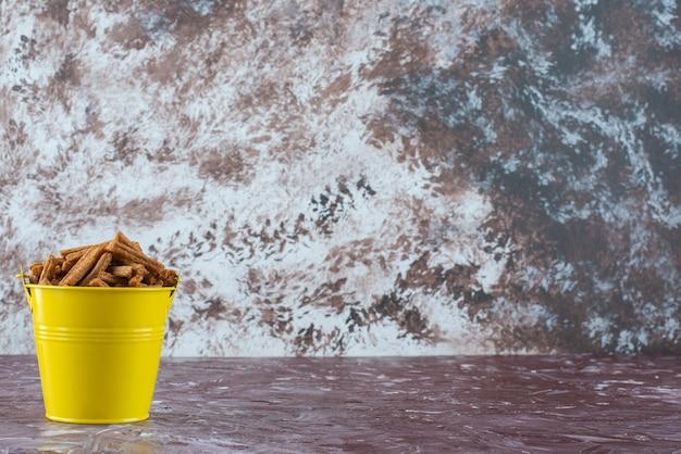 Knapperig paneermeel in een emmer op het marmeren oppervlak