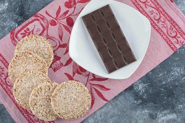 Knapperig rijstbrood met reep chocola op een tafelkleed.