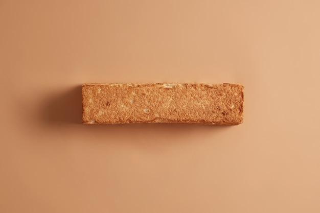 Knapperig zelfgebakken brood van tarwe van bovenaf gefotografeerd. beige achtergrond. bakkerij en voedselconcept. biologisch eetbaar product met veel koolhydraten. gezonde voeding. kopieer ruimte voor uw promo