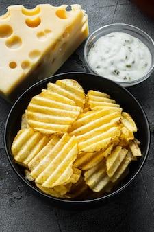 Knapperige aardappelchips gezet met kaas en ui, met dipsauzen, op grijze steen
