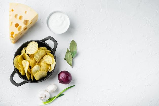 Knapperige aardappelchips met kaas en ui, met dipsauzen, tomaat dip zure room, op witte stenen ondergrond, bovenaanzicht plat leggen