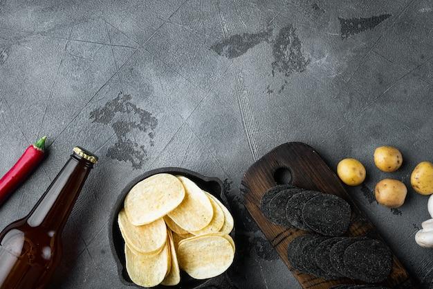 Knapperige aardappelchips set, met dipsauzen, op grijze stenen tafel, bovenaanzicht plat leggen