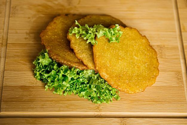 Knapperige aardappelpannenkoekjes met groene salade. stapel aardappel beignets op een houten tafel