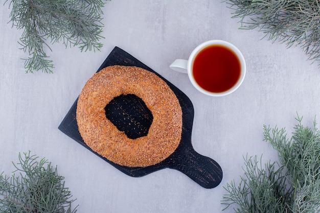 Knapperige bagel en een kopje thee op een witte achtergrond.