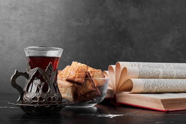 Knapperige barstjes in een glazen beker op zwarte achtergrond met een glas thee.