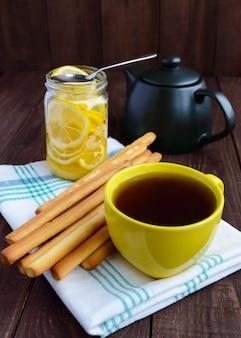 Knapperige broodstengels en thee met citroen op houten achtergrond. ontbijt