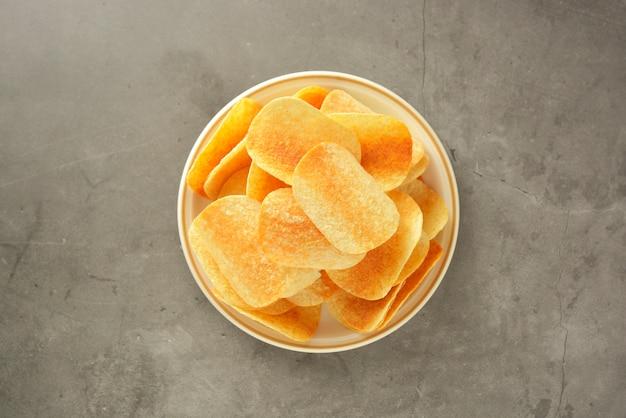Knapperige chips die over grijs worden geïsoleerd