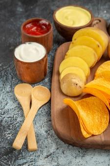Knapperige chips en ongekookte aardappelen op houten snijplank en verschillende kruiden op grijze tafel