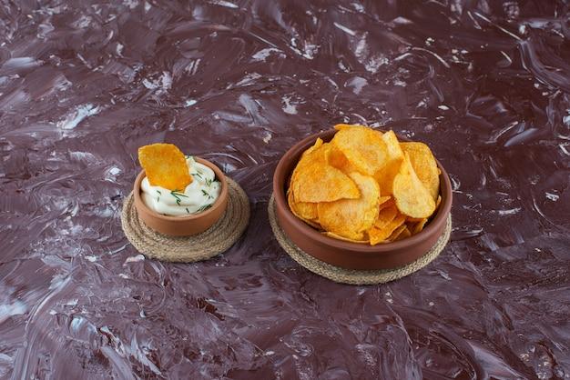 Knapperige chips en yoghurt in borden op onderzetters, op de marmeren tafel.
