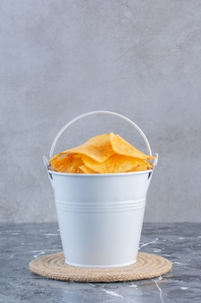 Knapperige chips in een emmer op onderzetter, op het marmeren oppervlak