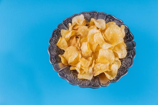 Knapperige chips in een zilveren kom op blauwe achtergrond.