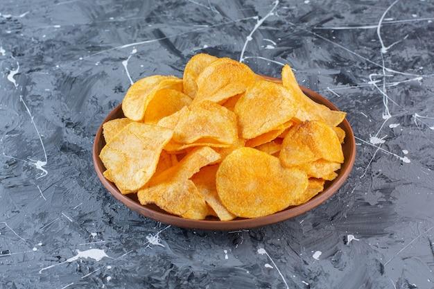 Knapperige chips in plaat, op het marmeren oppervlak