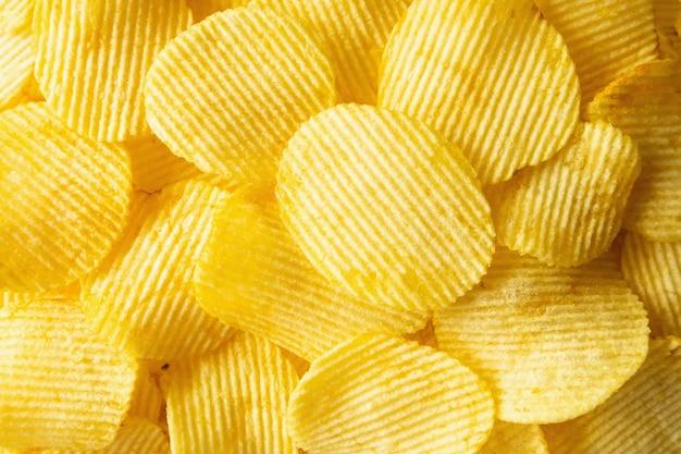 Knapperige chips snack textuur achtergrond close-up bovenaanzicht