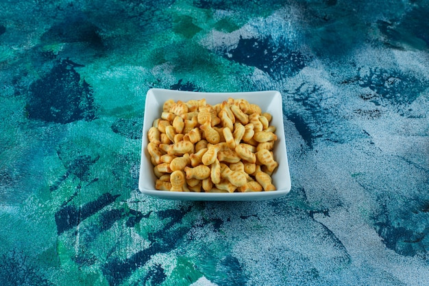 Knapperige cracker vis in een kom op blauw.