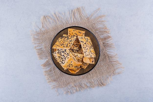 Knapperige crackers met zwarte zaden in een donkere glazen kom.