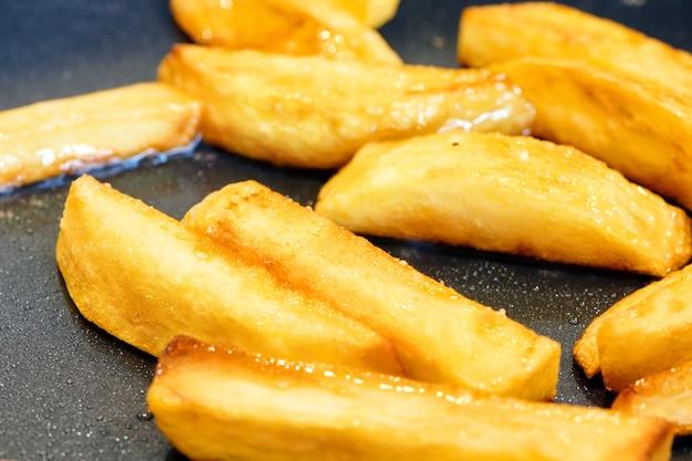 Knapperige en gouden frietjes. huisgemaakte gefrituurde chips. aardappel op pan braden. voedsel koken achtergrond. close-up bekijken met selectieve focus.