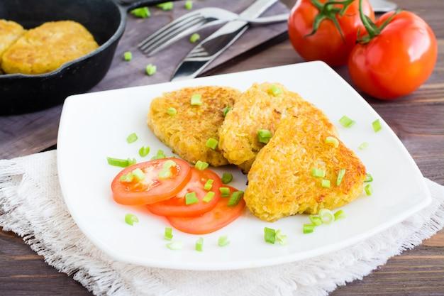 Knapperige gebakken aardappelen en tomaten op een plaat