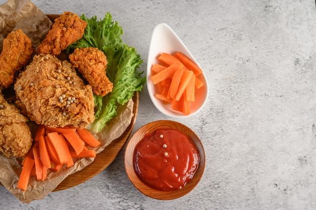 Knapperige gebraden kip op een houten plaat met tomatensaus en wortel